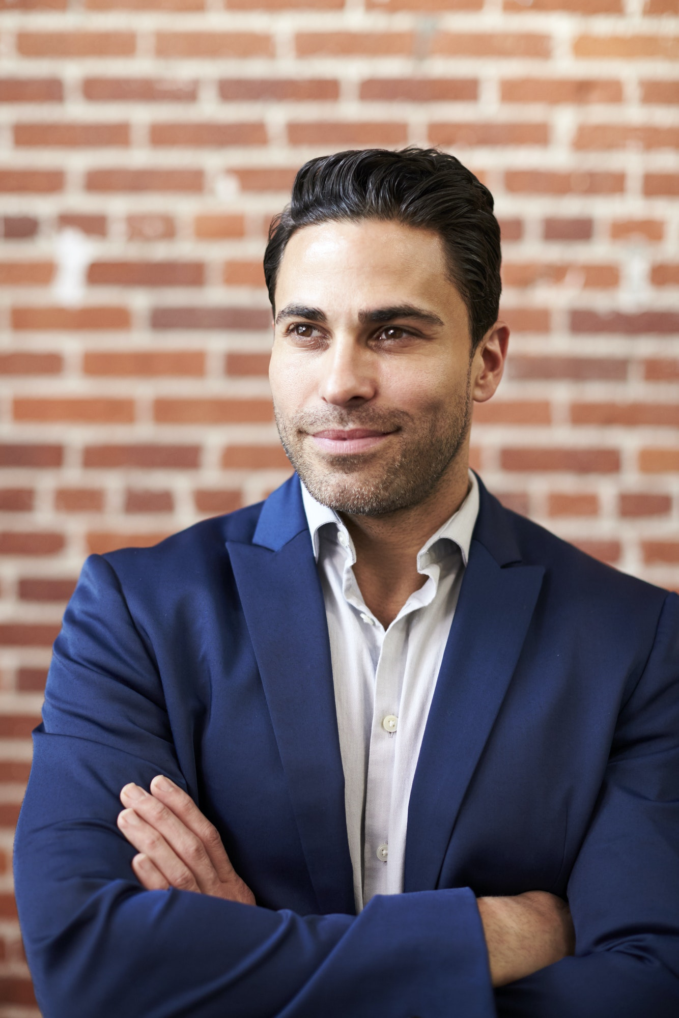 Smiling Mature Businessman Standing Against Brick Wall In Modern Office